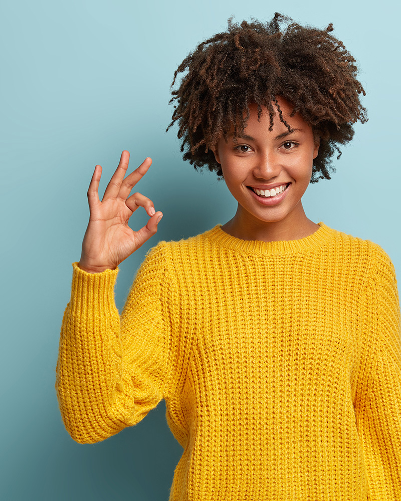 Okay, its fine. Charming good looking young Afro woman says no problem, shows excellent gesture, has tender smile, gives recommendation, demonstrates positive approval, dressed in yellow sweater